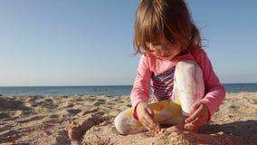 La bella bambina sta giocando con la sabbia sulla spiaggia sui precedenti del mare e del cielo blu archivi video