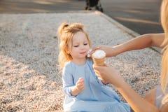 La bella bambina in un vestito blu che mangia un gelato, gli aiuti della mummia e pulisce la sua bocca immagine stock libera da diritti