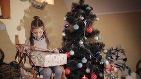 La bella bambina vicino ad un albero di Natale apre un contenitore di regalo con un regalo del ` s del nuovo anno da Santa Claus stock footage