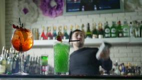 La bella bevanda alcolica con le fragole fresche sta sullo scrittorio della barra e su fondo del barista esegue l'acrobazia video d archivio