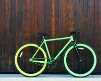 La bella bicicletta d'annata dell'ingranaggio fisso verde intenso sta in una parete di legno nera Fotografie Stock Libere da Diritti