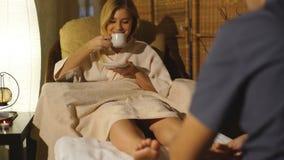 La bella bionda caucasica fa un massaggio del piede stock footage