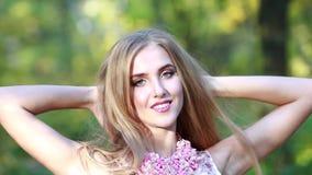 La bella bionda con capelli lunghi in un giorno elegante di autunno nel parco stock footage