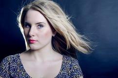 La bella bionda con gli occhi azzurri che esaminano seriamente un buio Fotografia Stock