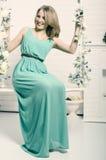 La bella bionda con gli occhi azzurri nel vestito verde su uno swin Immagini Stock