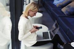 La bella bionda con i capelli di scarsità che si siedono in un caffè nel suo intervallo di pranzo, email di ricerche Fotografia Stock