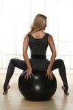 La bella bionda sexy con la figura esile atletica perfetta impegnata nell'yoga, nell'esercizio o nella forma fisica, conduce uno  Immagine Stock