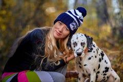 La bella bionda in un cappuccio tricottato cammina con il cane nel legno di autunno Fotografie Stock