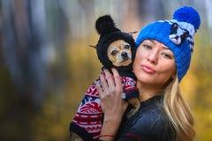 La bella bionda in un cappuccio tricottato cammina con il cane nel legno di autunno Fotografia Stock