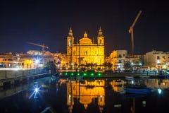 La bella chiesa di parrocchia di Msida alla notte profonda con il porto alla priorità alta malta Fotografia Stock Libera da Diritti
