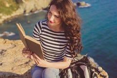 La bella donna è libro di lettura sul picco della roccia Immagini Stock Libere da Diritti