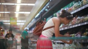 La bella donna è verdure di compera e frutta in supermercato, castana scelga i pomodori ed i cetrioli e li mette dentro archivi video