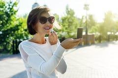 La bella donna adulta dipinge le labbra con rossetto, stante sul marciapiede fotografie stock