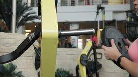 La bella donna aggiunge il peso sul disco rotondo alla macchina di forma fisica in palestra video d archivio