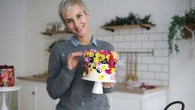 La bella, donna allegra nell'auto grigio della tenuta del maglione ha decorato il dolce con i fiori nello studio moderno bianco d archivi video