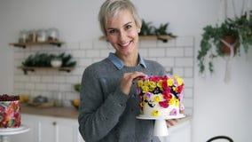 La bella, donna allegra nell'auto grigio della tenuta del maglione ha decorato il dolce con i fiori nello studio moderno bianco d video d archivio
