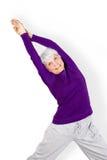 La bella donna anziana affascinante felice che fa gli esercizi mentre risolve il gioco mette in mostra Immagini Stock