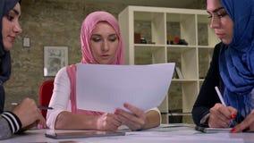 La bella donna araba nel hijab rosa sta avendo conversazione del lavoro con altre femmine musulmane che tengono i documenti, sede video d archivio