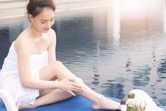 La bella donna asiatica con il corpo sfrega al bordo di nuoto del po fotografie stock libere da diritti