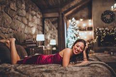 La bella donna asiatica felice sta sedendosi a letto a casa vicino all'albero di Natale nell'interno accogliente Interno con nata fotografia stock libera da diritti