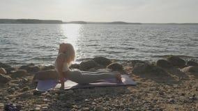 La bella donna atletica che fa gli esercizi di mattina sulla spiaggia Spiaggia ed alba sui precedenti stock footage