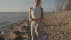 La bella donna atletica che fa gli esercizi di mattina sulla spiaggia Spiaggia ed alba sui precedenti archivi video