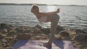 La bella donna atletica che fa gli esercizi di mattina sulla spiaggia Spiaggia ed alba sui precedenti video d archivio