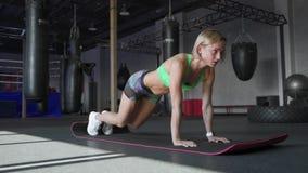 La bella donna atletica fa Spinta-UPS come componente della sua forma fisica trasversale, routine di addestramento della palestra stock footage