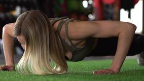 La bella donna atletica fa Spinta-UPS come componente della sua forma fisica trasversale, routine di addestramento della palestra archivi video