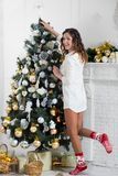 La bella donna attiva decora l'albero di Natale immagine stock libera da diritti
