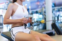 La bella donna attraente di forma fisica sta tirando il peso e la tenuta fotografia stock