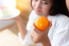 La bella donna attraente sta tenendo l'arancia ed il dolce Fa grazioso immagine stock libera da diritti