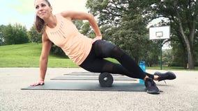 La bella donna ben preparata sta facendo gli esercizi con il rotolo della fascia archivi video