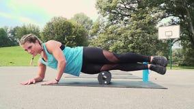 La bella donna ben preparata sta facendo gli esercizi con il rotolo della fascia stock footage