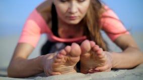 La bella donna bionda che fa l'allungamento si esercita sulla spiaggia Primo piano del piede stock footage