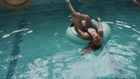 La bella donna bionda con la figura perfetta in vestito di nuoto nero sta nuotando sull'anello di gomma gonfiabile in stagno 4K archivi video