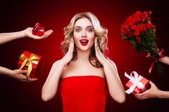 La bella donna bionda riceve i regali ed i fiori i giorni del ` s sulle donne del biglietto di S. Valentino e dell'internazionale Immagini Stock