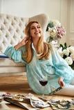 La bella donna bionda sexy si siede sull'album della famiglia di sguardi del pavimento Fotografia Stock