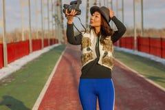 La bella donna in black hat fa un selfie della polaroid su un ponte nell'inverno in Europa immagini stock