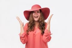 La bella donna in camicia rossa ha sorpreso e solleva le sue mani con il sorriso affascinante fotografie stock libere da diritti