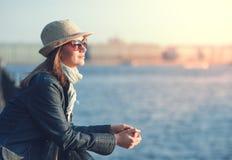 La bella donna in cappello e la sciarpa godono della luce solare nella città Fotografia Stock Libera da Diritti
