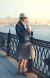 La bella donna in cappello e la sciarpa godono della luce solare nella città Immagini Stock