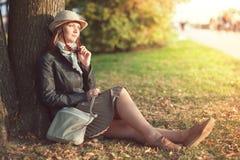La bella donna in cappello e la sciarpa godono della luce solare nella città Fotografia Stock