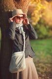 La bella donna in cappello e la sciarpa godono della luce solare nella città Fotografie Stock