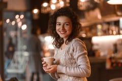 La bella donna castana di affari fa le note in suo blocco note in ristorante accogliente vestito nello sweather tricottato gray fotografia stock