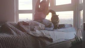 La bella donna castana felice sveglia la menzogne sul letto che sbadiglia di mattina con il suo gatto di procione lavatore di Mai stock footage