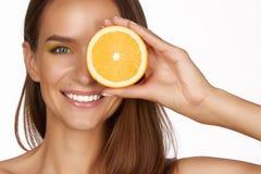 La bella donna castana sexy con l'agrume su un fondo bianco, l'alimento sano, l'alimento saporito, dieta organica, sorride sano Fotografie Stock Libere da Diritti