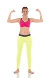 La bella donna castana sorridente mostra i muscoli delle mani Fotografie Stock Libere da Diritti