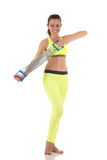 La bella donna castana sorridente negli sport gialli al neon costume scaldarsi il tricipite ed i muscoli del bicipite facendo uso Fotografia Stock