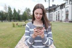 La bella donna castana sta leggendo qualcosa sul telefono cellulare che cammina vicino alla casa fotografie stock